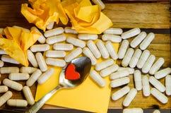 Mały czerwony serce w łyżce na kapsuła leku i kolor żółty notatce Zdjęcie Royalty Free