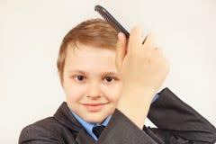 Mały dżentelmen szczotkuje jej włosianego hairbrush w eleganckim kostiumu Obrazy Royalty Free