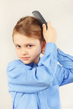 Mały dżentelmen szczotkuje jej włosianego hairbrush w jaskrawej koszula Obrazy Stock