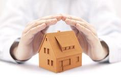 Mały dom ochraniający rękami zdjęcia stock