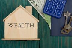 Mały dom z tekstem & x22; Wealth& x22; , klucze, kalkulator, paszport, pieniądze fotografia royalty free