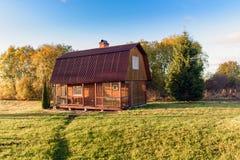Mały drewniany dom na zielonym polu i drzewach fotografia stock