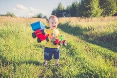 Mały dzieciak outdoors, pokazywać jego zabawkarskich samochody fotografia stock
