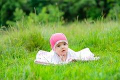 Mały dziecka lying on the beach w lecie na trawie w ogródzie obraz royalty free