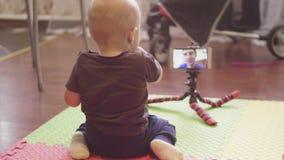 Mały dziecka obsiadanie na podłoga komunikuje na wideo wezwaniu w smartphone z jego caucasian ojcem Salowi 4K popierają zbiory wideo