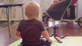 Mały dziecka obsiadanie na podłoga komunikuje na wideo wezwaniu w smartphone z jego caucasian ojczulkiem Salowi 4K popierają zbiory wideo