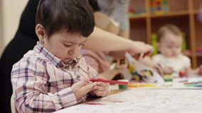 Mały dziecka obsiadanie przy stołem, mienie czerwony markier, decyduje co rysować, w tle, dzieci maluje dalej zbiory