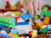 Mały dziecka ` s ręki podnosić/wybiera kawałek kolorowe łączy plastikowe cegły obrazy royalty free