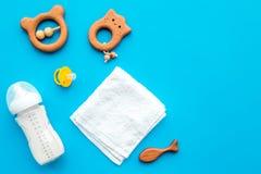 Mały dziecka tło Drewniane zabawki, pacyfikator, butelka, ręcznik na błękitnym tło odgórnego widoku copyspace zdjęcia royalty free
