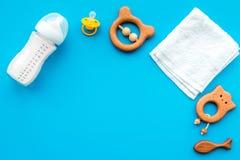 Mały dziecka tło Drewniane zabawki, pacyfikator, butelka, ręcznik na błękitnym tło odgórnego widoku copyspace fotografia royalty free