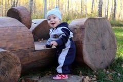 Mały dziecko drewniane bele uśmiechnięty lato z drewnianą maszyną w parku zdjęcia stock