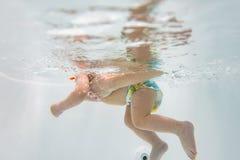Mały dziecko pływa pod wodą dziecko angażuje w akwalungu pikowaniu zdjęcia royalty free
