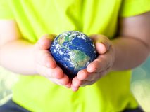 Ma?y dziecko trzyma planety ziemi? w ona w zielonej koszulce r?ki br?zowi? dzie? zakrywaj?c? ziemi? ?rodowiskowy ulistnienie idzi obraz royalty free