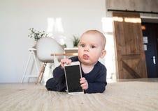 Mały dziecko trzyma telefon komórkowego Dziecko z telefonem Gadżet jest w rękach dziecko Fotografia Stock