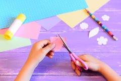Mały dziecko tworzy kartka z pozdrowieniami dla mamy krok Dziecko trzyma nożyce i ciie kwiatu od papieru Materiały dla kreatywnie Zdjęcia Stock
