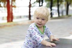 Mały dziecko uczy się chodzić blisko ławek, berbeć Fotografia Stock