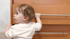 Mały dziecko, uczy się chodzić, trzymający rękojeść szafa, w dziecko pokoju Fotografia Stock