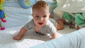 Mały dziecko w ściąga śmia się i próby czołgać się Szczęśliwy dzieciństwo, dziecięca radość pierwsi kroki w życiu zbiory