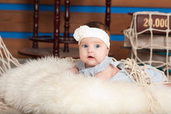 Mały dziecko w białej kapitałce. Kłamać indoors Zdjęcie Royalty Free