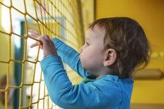 Mały dziecko w koszulki błękitnych spojrzeniach przez żółtej siatki obraz stock