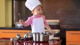 Mały dziecko w szefa kuchni kostiumu pomaga jej macierzystego kucharza w kuchni zdjęcie wideo