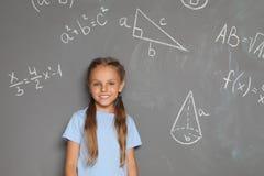 Mały dziecko w wieku szkolnym i matematycznie formuły obraz royalty free