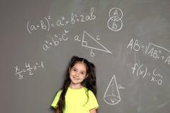 Mały dziecko w wieku szkolnym i matematycznie formuły zdjęcie stock