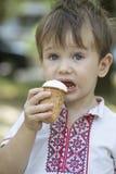 Mały dziecko z dużymi niebieskimi oczami je lody Obrazy Stock