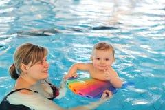 Mały dziecko z niebieskimi oczami uczy się pływać obrazy stock