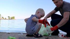 Mały dziecko zbiera grat na plaży Jego tata wskazuje jego palec gdzie rzucać śmieci Rodzice uczą dzieciom czystość zbiory