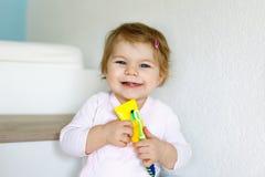 Mały dziewczynki mienia toothbrush i szczotkować pierwszy zęby Berbeć uczy się czyścić dojnego ząb Obrazy Stock