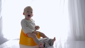 Mały emocjonalny dziecko chłopiec obsiadanie na chamberpot i śmiechy w jaskrawym pokoju zbiory wideo