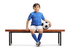 Mały futbolisty obsiadanie na ławce obrazy royalty free