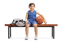 Mały gracza koszykówki obsiadanie na drewnianej ławce obok spo obraz stock