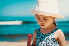 Mały i śliczny dziewczyny łasowania lody na plaży Zdjęcie Stock