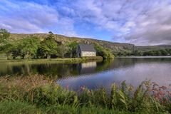 Mały irlandzki kościół na półwysepie przed wzgórzami z kwitnąć kwiaty i paproci - St Finbarr ` s krasomówstwo obraz royalty free