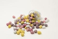 Mały jaskrawy coloured cukier pokrywał czekoladowych Wielkanocnych jajka rozlewa out od i wspiera kształtną szklaną filiżankę zdjęcie royalty free