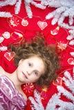 Mały jasnogłowy dziewczyny lying on the beach na czerwonej podłoga z Bożenarodzeniową girlandą i jedlinowych gałąź wokoło ona kie Zdjęcia Royalty Free