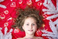 Mały jasnogłowy dziewczyny lying on the beach na czerwonej podłoga z Bożenarodzeniową girlandą i jedlinowych gałąź wokoło ona kie fotografia stock