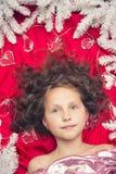 Mały jasnogłowy dziewczyny lying on the beach na czerwonej podłoga z Bożenarodzeniową girlandą i jedlinowych gałąź wokoło ona kie Obraz Royalty Free