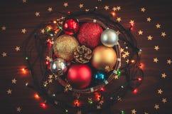 Mały koszykowy pełny Bożenarodzeniowe dekoracje, piłki, rożek z rozjarzoną girlandą i złoci gwiazda confetti, zdjęcia stock