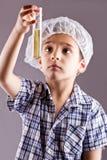 Mały męski dziecko eksperyment z próbnymi tubkami Obraz Stock