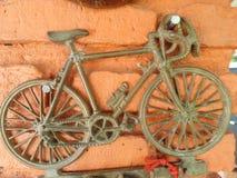 Mały mosiężny rowerowy pamiątkarski inkasowy obwieszenie w pomarańczowej colour ścianie Obraz Stock