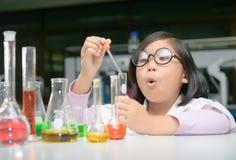 Mały naukowiec w lab żakiecie robi eksperymentowi Zdjęcie Stock