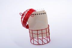 Mały notatnik umieszczający w czerwonego koloru ptaka domu Obraz Stock