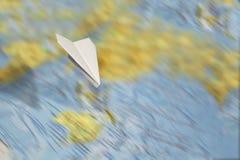 Mały papieru samolot lata nad zamazaną abstrakcjonistyczną geographical mapą świat fotografia royalty free