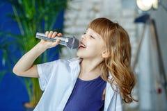Mały pięknego dziecka śpiew w mikrofon przeciw jako tła popasu pojęcia dolarom szarość wiesza haczyka zdjęcia royalty free