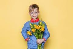 Mały piękny dziecko z bukietem tulipany Syn daje mama kwiaty na kobiety ` s dniu, Macierzysty ` s dzień Urodziny to walentynki dn Fotografia Stock