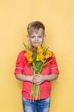 Mały piękny dziecko z różową koszula daje bukietowi kwiaty na kobiety ` s dniu, Macierzysty ` s dzień Urodziny to walentynki dni  Obraz Royalty Free