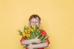 Mały piękny dziecko z różową koszula daje bukietowi kwiaty na kobiety ` s dniu, Macierzysty ` s dzień Urodziny to walentynki dni  Obraz Stock